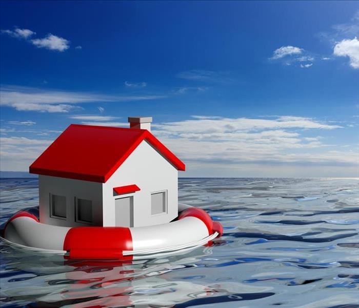 toy house floating inside life preserver on the ocean